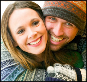 A young male and female couple embraces and smiles for the camera. Magi Astrology helps people to indentify true love.