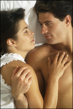 Lovers relaxing in bed gaze into each other's eyes. Magi astrology helps to find both great sex and true love.